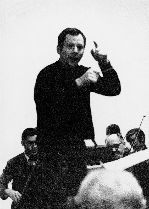 Rudolf Konrad Lienert, von 1965 bis 1970 Dirigent des Orchesters, während einer Probe. Im Hintergrund, leicht versteckt sichtbar, von der ersten Violine Max Leuthold, Ehrenmitglied, und P. Reinhard Peter. Aufnahme von 1967.